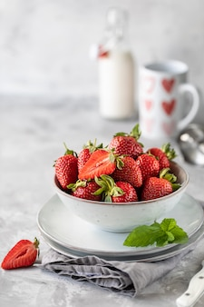 Fresas frescas en un tazón y ramitas de menta en una mesa de hormigón blanco.