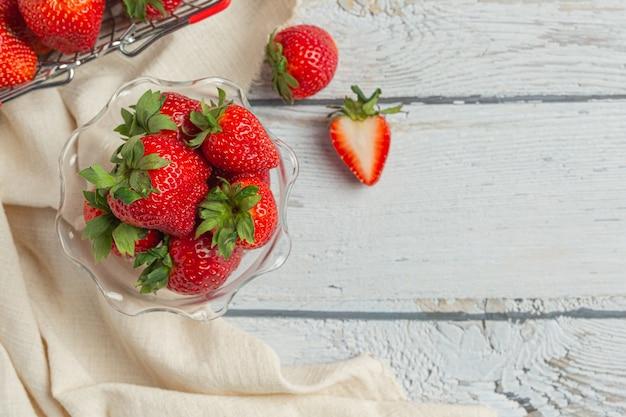 Fresas frescas en vidrio sobre mesa de madera