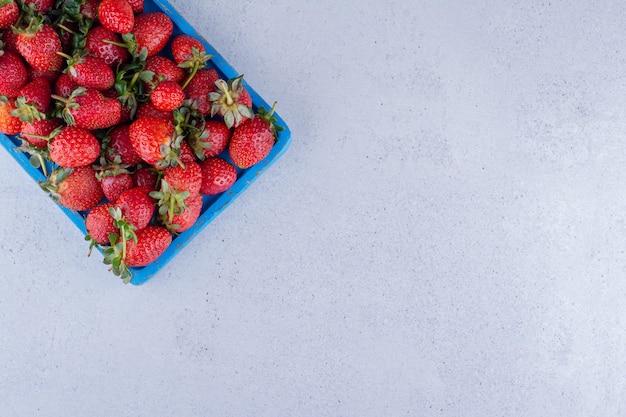 Fresas jugosas amontonadas en una bandeja azul sobre fondo de mármol. foto de alta calidad