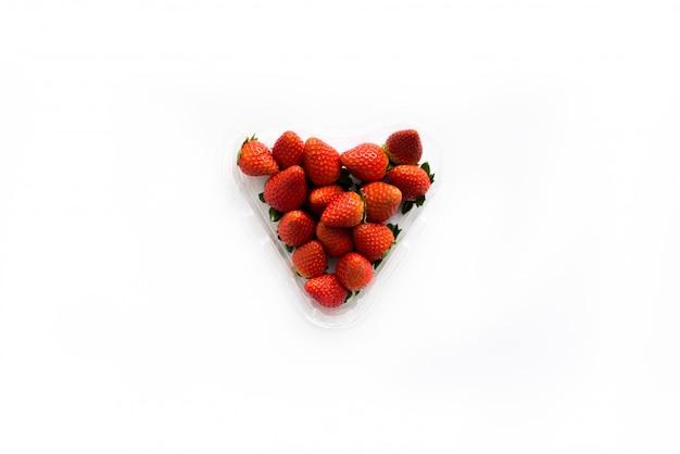 Fresas jugosas frescas en una caja en forma de corazón