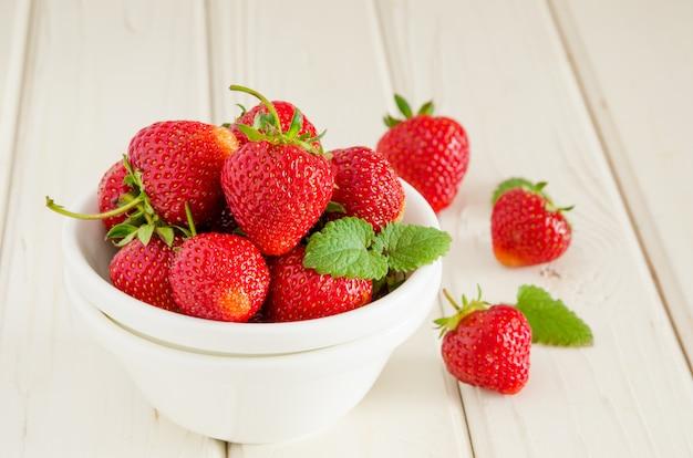 Fresas maduras frescas en un recipiente sobre un fondo blanco de madera.