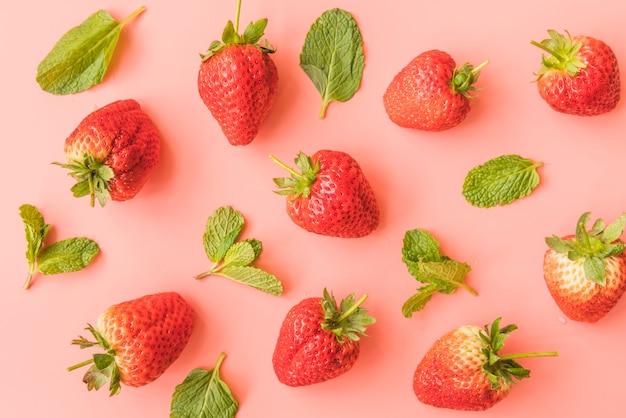 Fresas maduras y hojas de menta en el fondo