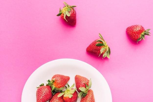 Fresas maduras con hojas en placa