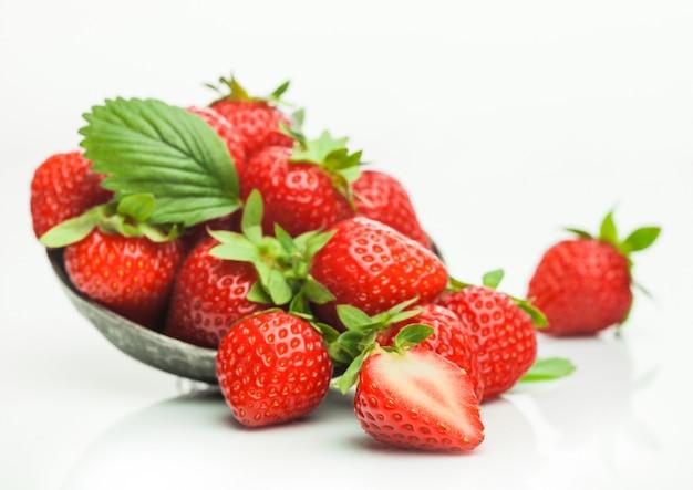 Fresas orgánicas crudas frescas con hoja en placa de tazón de acero sobre fondo blanco.