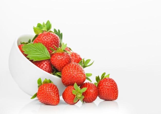Fresas orgánicas crudas frescas en plato de tazón de cerámica blanca sobre fondo blanco.