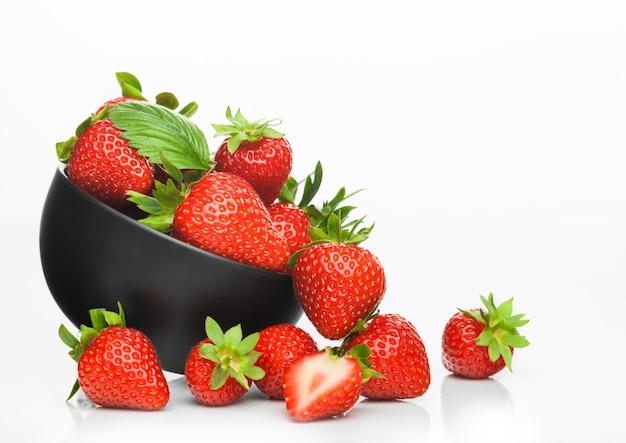 Fresas orgánicas crudas frescas en plato de tazón de cerámica negra sobre fondo blanco.