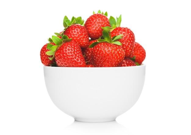 Fresas orgánicas crudas frescas en un tazón de cerámica blanco aislado sobre fondo blanco.