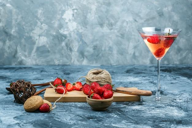 Fresas de primer plano y un cuchillo en la tabla de cortar con una copa de cóctel, ovillo, un cuenco de fresas y cucharas de madera sobre fondo de mármol azul oscuro. espacio libre horizontal para su texto