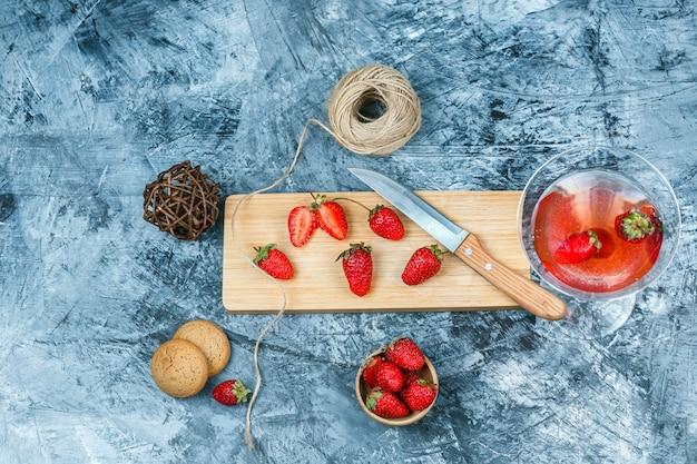 Fresas de primer plano y un cuchillo en la tabla de cortar con una copa de cóctel, ovillo, un tazón de fresas y galletas sobre fondo de mármol azul oscuro y gris. espacio libre horizontal para su texto