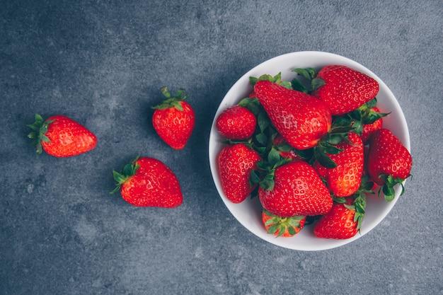 Fresas en un recipiente sobre un fondo gris con textura. vista superior.