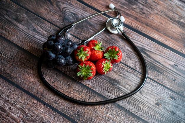 Fresas rojas escocesas y uvas negras con estetoscopio en la parte superior de la mesa de madera