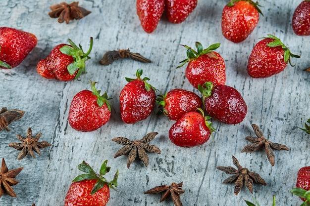 Fresas rojas frescas y clavo en la superficie de mármol