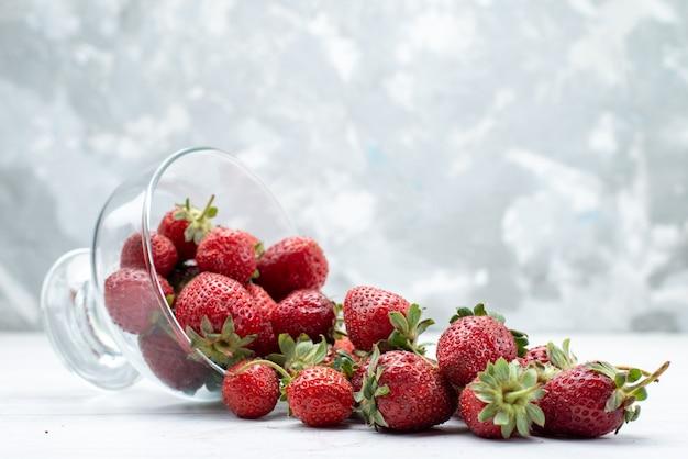 Fresas rojas frescas dentro y fuera de la placa en blanco, fruta baya fresca foto suave
