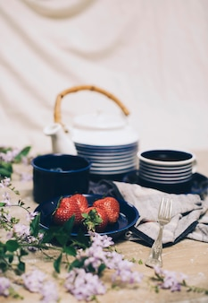 Fresas rojas; juego de té y desenfoque de flores en el escritorio de madera