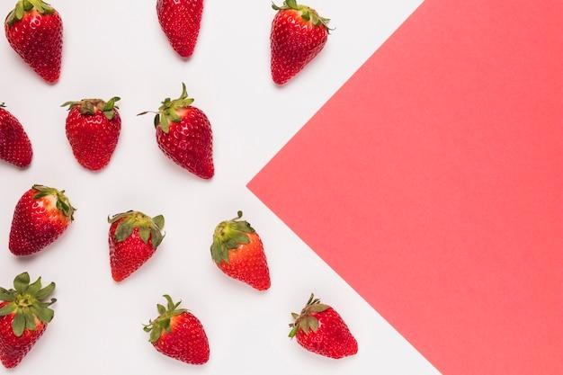 Fresas rojas maduras sobre fondo multicolor rosa y blanco