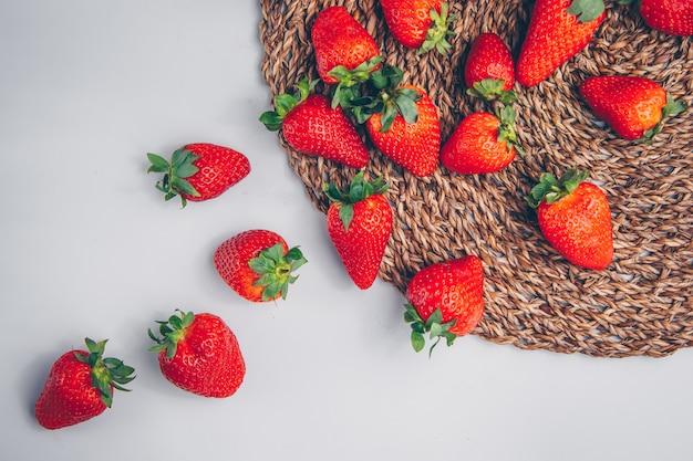 Fresas en un salvamanteles y fondo blanco. vista superior.