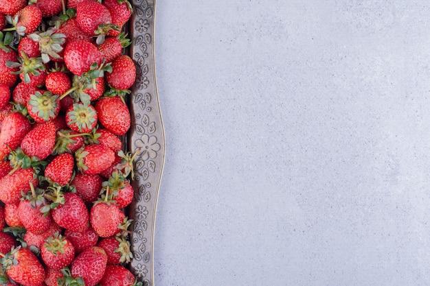 Fresas servidas en una fuente ornamentada sobre fondo de mármol. foto de alta calidad