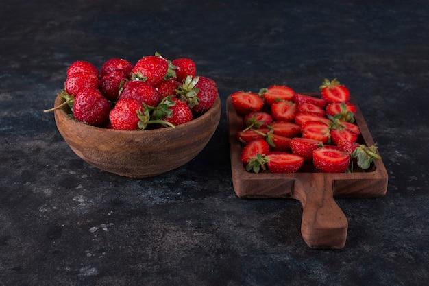 Fresas en una tabla de madera y en un plato