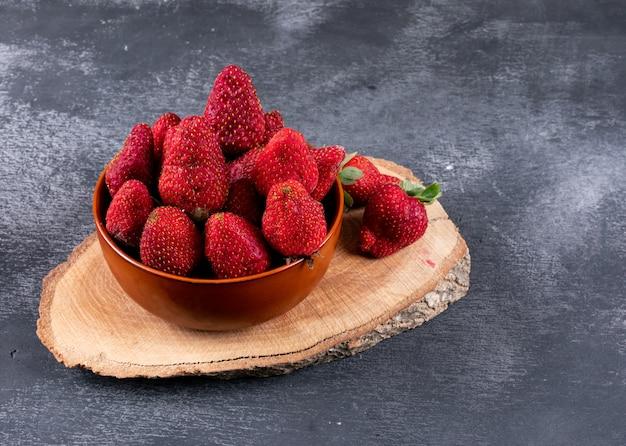 Fresas en un tazón sobre un trozo y una mesa oscura
