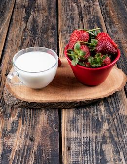 Fresas en un tazón con una taza de leche en un trozo y mesa de madera