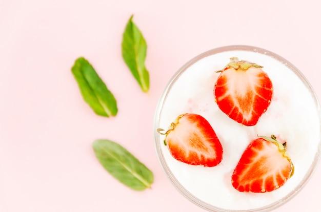 Fresas con yogur y hojas verdes.