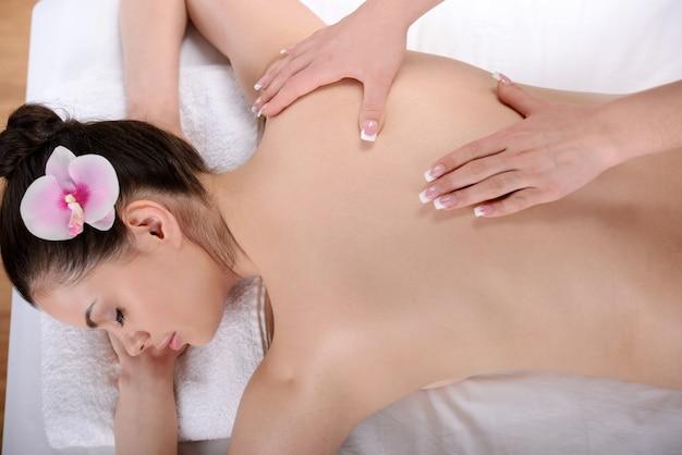 Fresca y hermosa mujer morena tomando masaje.