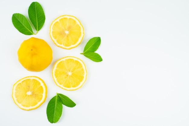 Fresca rodaja de limón con hojas, suplemento de vitamina c natural sobre fondo blanco.