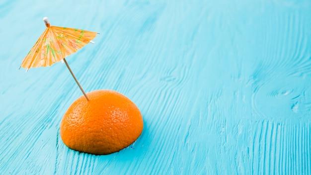 Fresca rodaja de naranja con sombrilla decorativa