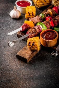 Fresco, cocinado en casa a la parrilla carne de fuego shish kebab de carne con verduras y especias, con salsa de barbacoa y salsa de tomate,