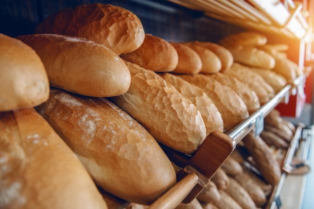 Frescos deliciosos panes de pan en fila en los estantes listos para la venta. panadería interior.