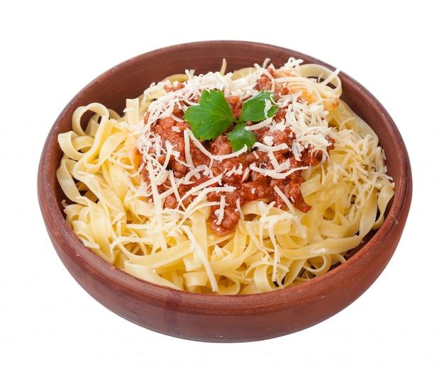 Frescos y deliciosos spagetti a la boloñesa sobre fondo blanco.