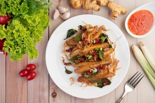 Fried chicken feet con hierbas en un plato blanco y salsa de inmersión.