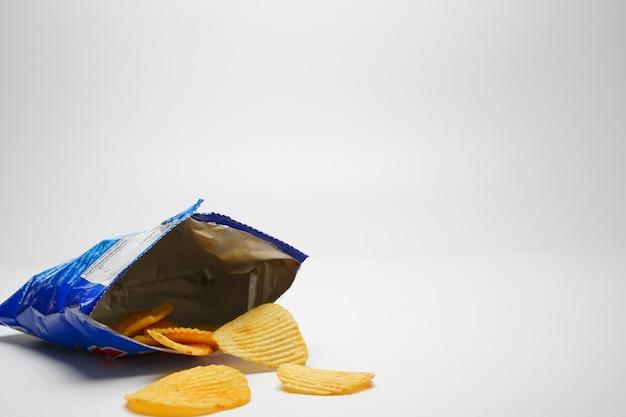Fried potato chips se derraman abriendo bolsas de plástico azules sobre fondo blanco.
