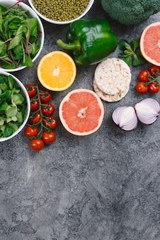Frijol mungo espinacas; fruta cítrica; pastel de arroz inflado y verduras frescas sobre fondo concreto