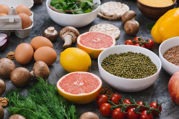 Frijol mungo; pomelos; huevos y verduras sobre fondo de hormigón.