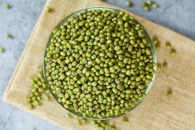 Frijol mungo verde en un tazón sobre fondo gris - cereales integrales de semillas de frijol mungo