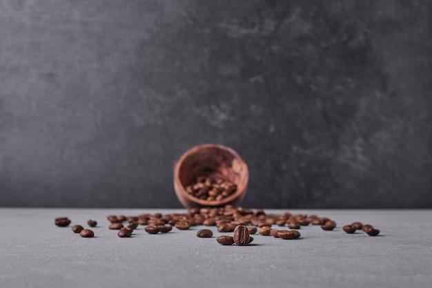 Frijoles arábica marrón sobre fondo gris.