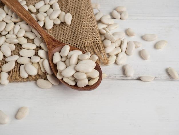 Frijoles blancos en una cuchara de madera sobre una mesa de madera blanca, espacio de copia