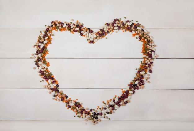 Frijoles, lentejas y frijoles dispuestos en forma de corazón sobre un fondo blanco de madera