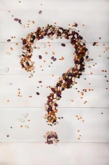 Frijoles, lentejas, guisantes dispuestos sobre un fondo blanco de madera en forma de signo de interrogación