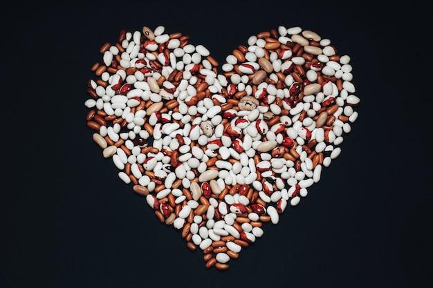 Frijoles multicolores en forma de corazón sobre un fondo negro. frijoles marrones y blancos