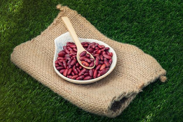 Frijoles rojos de cereales en un tazón de madera y una cuchara en la pared de hierba