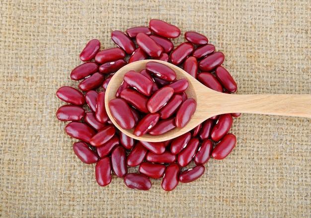 Frijoles rojos en cuchara de madera sobre fondo de saco