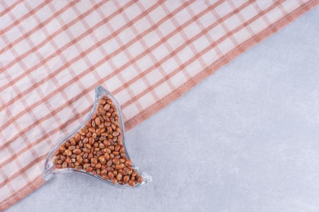 Frijoles rojos en un plato pequeño y triangular sobre un mantel, sobre una superficie de mármol