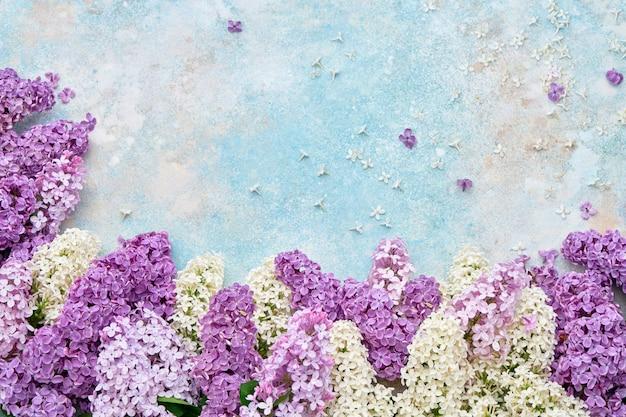 Frontera colorida de las flores de la lila en fondo en colores pastel.