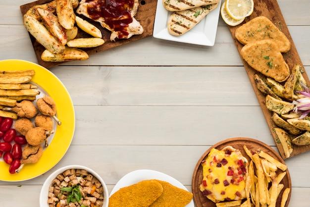 Frontera hecha de platos de pollo de comida rápida en mesa de madera