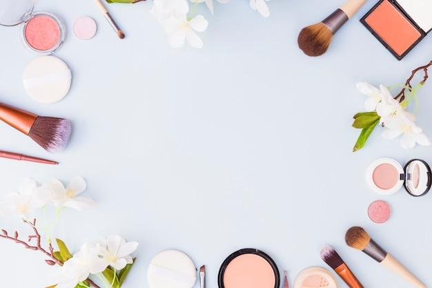 Frontera hecha con productos cosméticos y flores sobre fondo azul