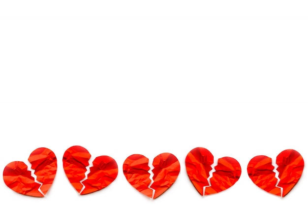 Frontera de muchos corazones rotos de papel rojos sobre fondo blanco. concepto de amor divorcio.