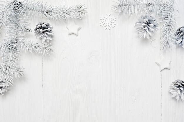 Frontera de ramas de árbol blanco de marco de navidad sobre fondo de madera