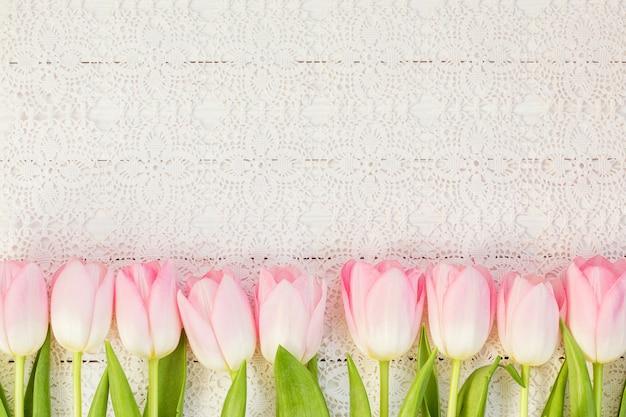 Frontera de tulipanes rosados en el mantel blanco de la vendimia